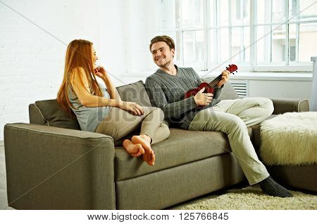 Young boyfriend play ukulele love song for his girlfriend in living room