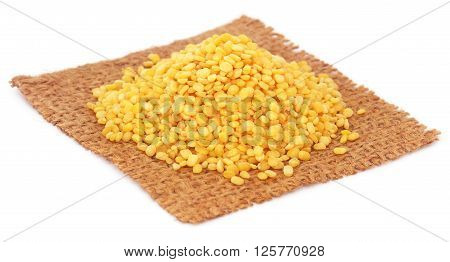 Dry mung bean on jute sack over white background