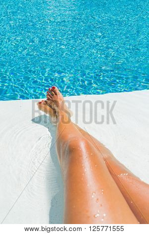 Female legs in the pool water selective focus