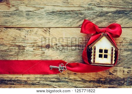 plywood small house with red ribbon and key on old wooden table