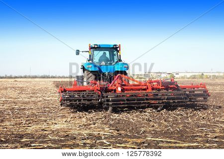 Tractor working in a field on a bright sunny day