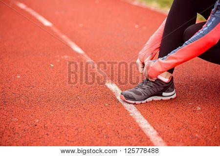 Woman Runner Tying Her Shoe