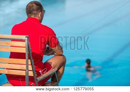 Lifeguard in chair overlooking swimming pool, rear view