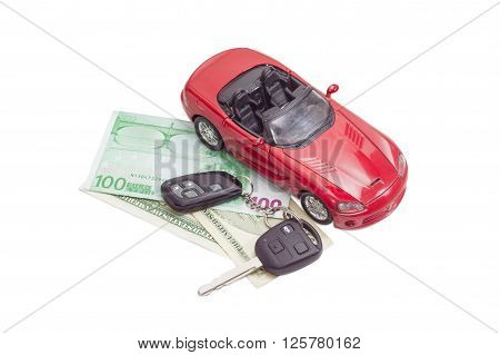 Red toy car cabriolet and car keys on the background of dollar and euro banknotes on a light background