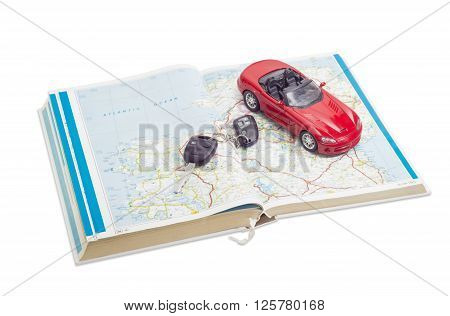 Red toy car cabriolet and car keys on the old open road atlas
