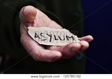 closeup of the hand of an old man with a piece of paper with the word asylum, with a dramatic effect