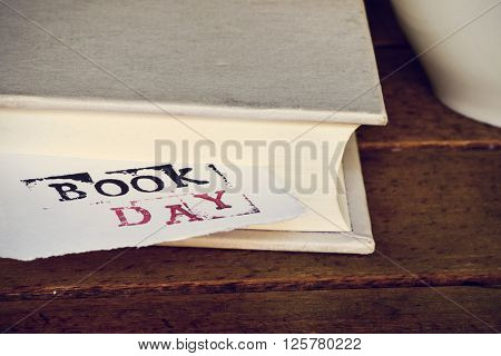 closeup of a a piece of paper wit the text book day popping up from a book, placed on a rustic wooden table next to a cup of coffee or tea