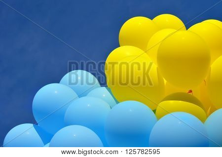blue and yellow balloons in the city festival on blue sky background