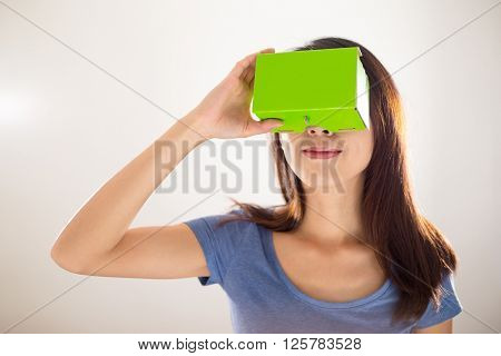 Woman looking though green card board of VR device