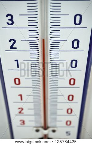 Aged outdoor thermometer in the retro design measuring mild temperature of twenty degrees of Celsius