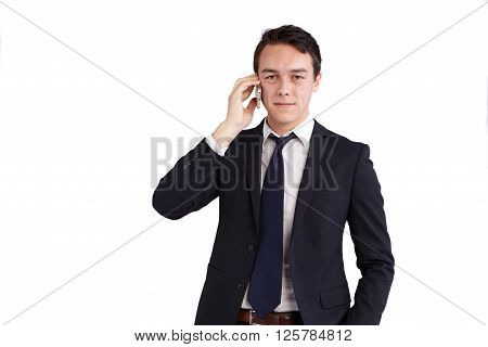 A young caucasian male businessman smiling holding a mobile phone looking at camera.