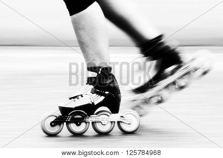 Speed skating - A roller skater is racing down the road detail of leg and skates.