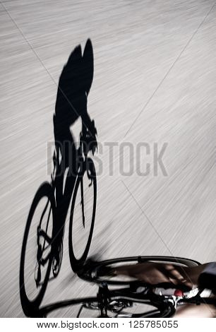 Speedy shadow - Bicycle racing down the road at the ironman triathlon in Zurich.