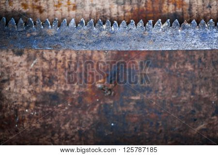 Color image of a hacksaw on a wooden plank.