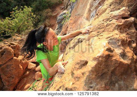 young woman rock climber climbing at mountain rock