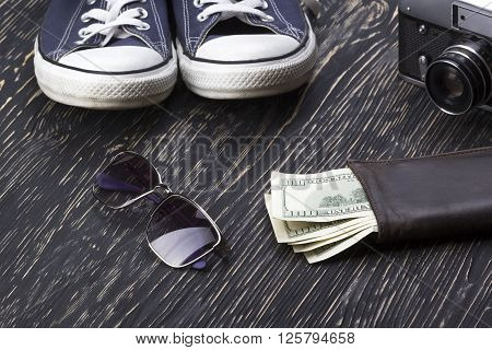 Men's accessories: wallet, sneakers, sunglasses and camera on wooden background