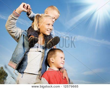 Crianças felizes ao ar livre.Família saudável tendo Fun.Over claro céu azul