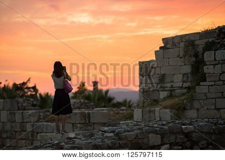 Selcuk Turkey - Jul 02 2015: Silhouette of a young lady standing in ruins of old castle and taking photo of orange sky during summer sunset.