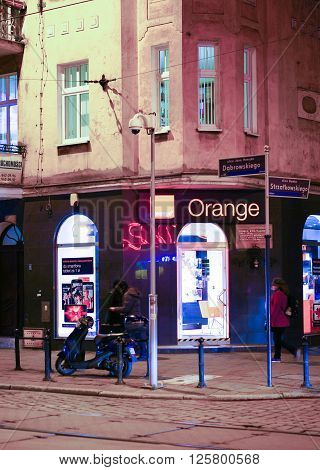 POZNAN POLAND - DECEMBER 05 2013: People close by a Orange telephone company salon in the city center by night