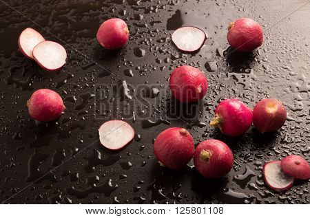 fresh radishes in a wet background close up view.