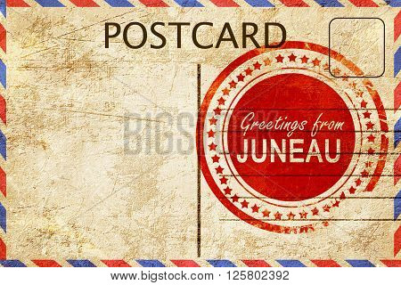 greetings from juneau, stamped on a postcard
