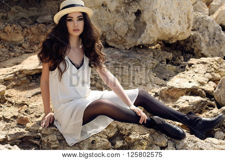 fashion outdoor photo of beautiful girl with dark hair wears casual elegant clothes and hat posing at summer seacoast