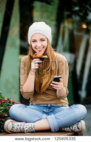 Teenager - young woman eating muffin in street and looking in phone