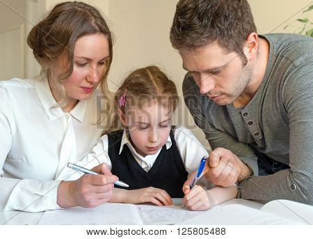 Mother And Father Helping Daughter With Homework At Home.