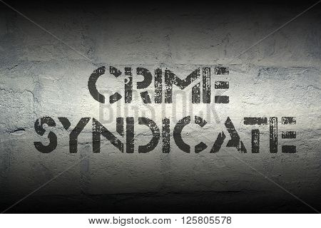 crime syndicate stencil print on the grunge white brick wall