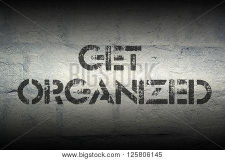 get organized stencil print on the grunge white brick wall
