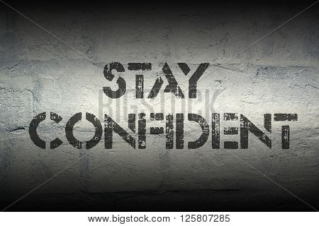 stay confident stencil print on the grunge white brick wall