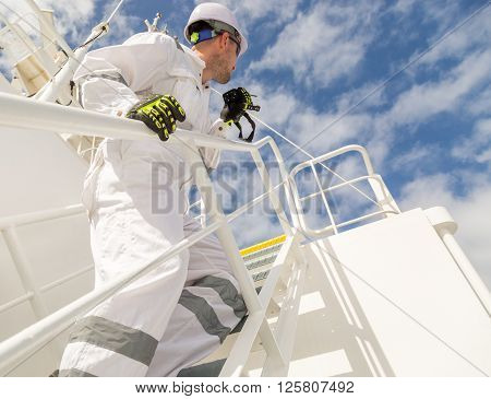 Man in white workwear with VHF standing on stairs