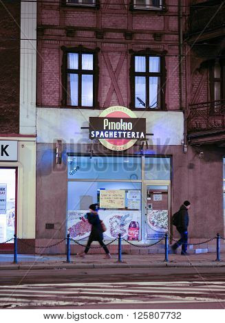POZNAN POLAND - DECEMBER 05 2013: People passing a Pinokio Spaghetteria offering pizza and pasta in the city center by night