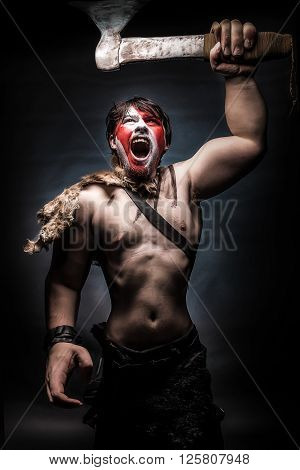 Painted image of man in war paint with an ax in his hand a warrior brandishing an ax furiously screaming barbarian of ancient times Viking and savage.
