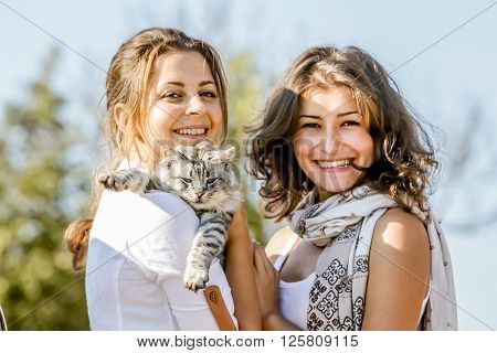 outdoor portrait of young two happy women with cat on natural background on farm