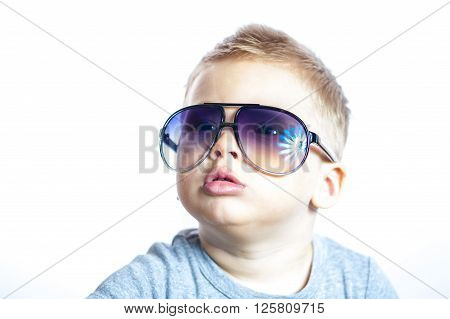Portrait of three year old boy in sunglasses isolated on white background.