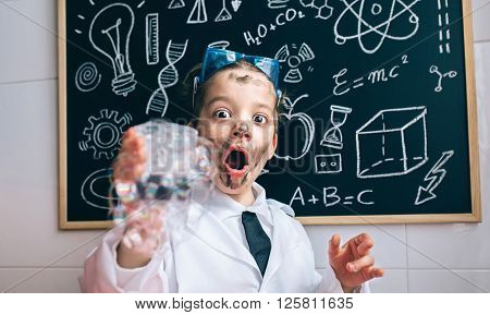 Close up of excited little scientist with dirty face holding glass with soap foam against of blackboard with drawings