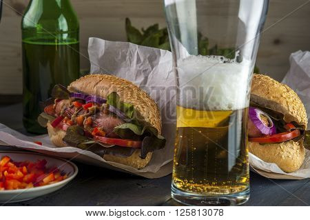 Beer glass and two hotdogs with grilled sausage and vegetables. Fast food. Selective focus.