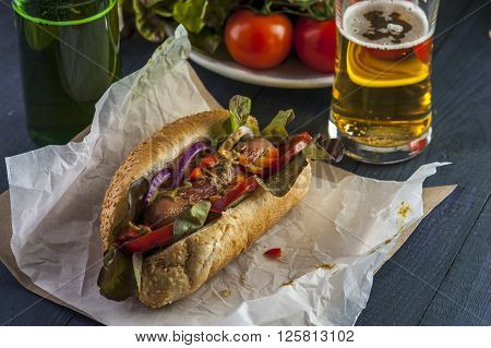 Hotdog with vegetables and sausage beer bottle and glass on wooden table. Selective focus.