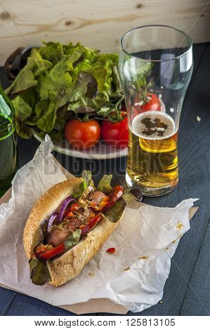 Tasty hotdog glass of beer and fresh vegetables on wooden table. Fast food.