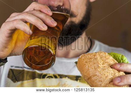 Bearded Man drinking beer and eating hotdog. Fast food. Selective focus.