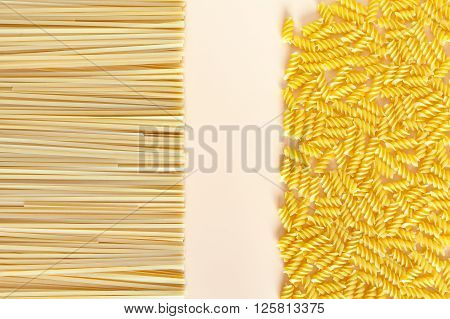 Raw pasta on a beige background with copy space. Place for signature. Spaghetti. Healthy product. Meal Gluten free.
