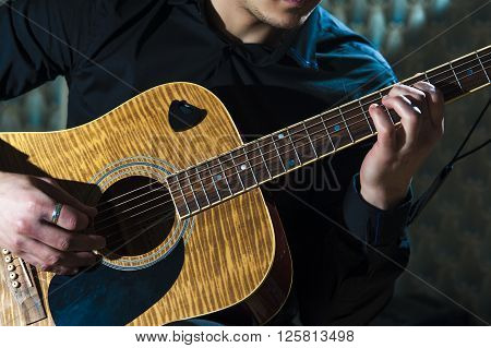 Young musician playing on acoustic guitar, horizontal view