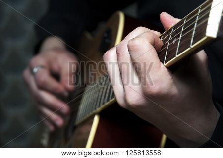 Closeup of acoustic guitar in man's hands.