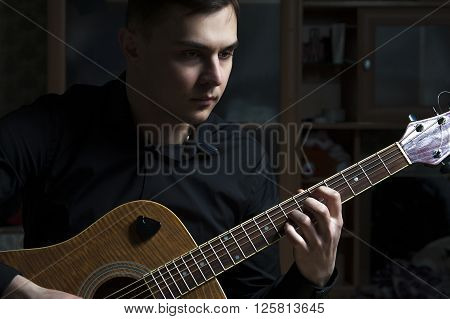 Young attractive guitarist playing on acoustic guitar