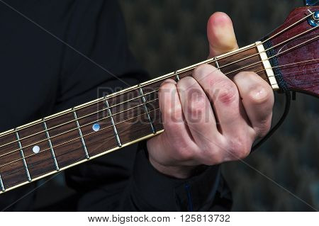 Man's hands playing on acoustic guitar closeup.
