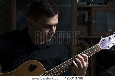 Portrait of young man playing on guitar