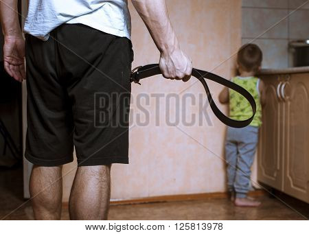 Aggressive parent with belt and frightened child in corner. Domestic violence.