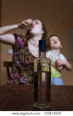 Depressive woman drinking alcohol and crying child in her hands. Female alcoholism. Focus on bottle.