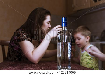 Quarrel between drunk mother and her little son. Family problems female alcoholism. Focus on bottle.